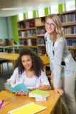 得到帮助的学生从家庭教师在图书馆里 免版税图库摄影