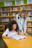 得到帮助的学生从家庭教师在图书馆里 库存图片