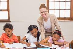 得到帮助的逗人喜爱的学生从老师在教室 免版税库存照片