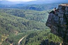 得到年轻人的远足者在山顶部坐高处和启发由惊人的看法 - 宽射击与 免版税库存图片