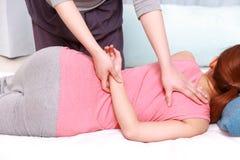 得到按摩脊柱治疗者的妇女 库存图片
