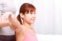 得到按摩脊柱治疗者的年轻日本妇女 免版税库存图片