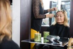 得到新的发型的妇女在客厅里 免版税库存图片