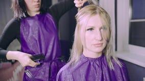 得到新的理发的少妇由美发师在客厅或家 股票录像