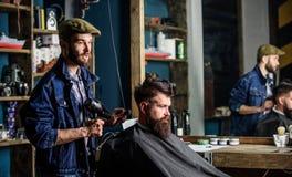得到有胡子的人修饰在有吹风器的美发师,当坐在椅子在理发店时 行家概念 库存照片