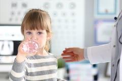 得到水的逗人喜爱的女孩在医生办公室 库存图片