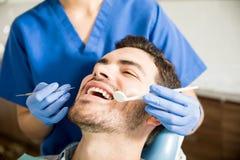 得到治疗的人从牙齿诊所的牙医 库存照片