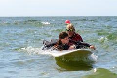 得到海浪教训的年轻十几岁的女孩在度假 免版税库存照片