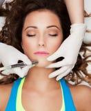 得到激光面孔治疗的妇女 免版税库存照片