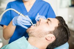 得到牙齿治疗的人从诊所的牙医 库存图片