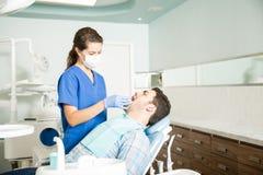 得到牙齿治疗的患者从诊所的牙医 免版税库存照片
