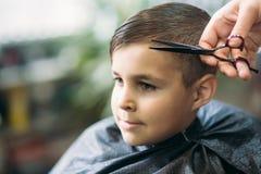 得到理发的Little男孩由理发师,当坐在椅子在理发店时  免版税库存图片