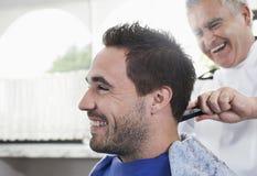 得到理发的人从理发师 免版税库存照片