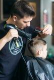 得到理发的小男孩由理发师,当坐在椅子在理发店时  库存图片