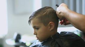 得到理发的小男孩由理发师,当坐在椅子在理发店时 股票视频