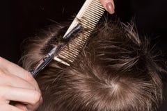 得到理发的逗人喜爱的小男孩侧视图由美发师在t 免版税库存图片