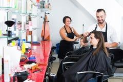 得到男性美发师的发型愉快的妇女 免版税库存照片