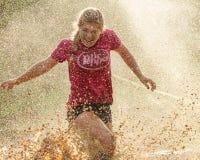 得到的妇女飞溅由泥矿 图库摄影