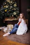 得到的毯子的年轻俏丽的深色的女孩温暖在冷的冬天,生活方式人 图库摄影