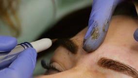 得到眼眉纹身花刺的年轻美女 眼眉的永久构成在发廊 慢的行动 影视素材