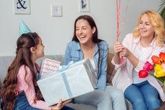 得到礼物和气球的在家一起祖母母亲和女儿生日坐的女孩从家庭 库存图片