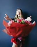 得到红色郁金香的花束逗人喜爱的女孩 给郁金香的男朋友 免版税库存照片