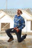 得到背部受伤的建筑工人 免版税库存照片