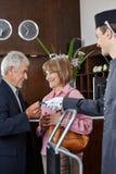 得到钥匙卡片的资深夫妇在旅馆里 免版税库存照片