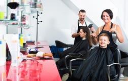 得到头发的小孩由妇女美发师切开了 免版税库存照片