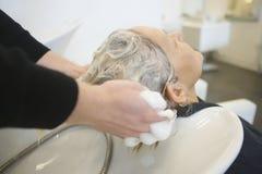 得到头发的资深妇女洗在客厅里 免版税库存照片