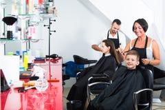 得到头发的高兴的孩子由妇女美发师切开了 免版税图库摄影