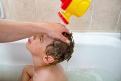 得到头发洗涤的小孩 库存图片