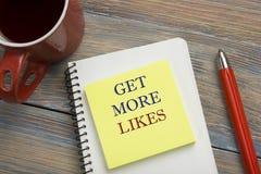 得到更多喜欢概念 与文本、红色铅笔和咖啡杯的笔记本页 办公桌台式视图 免版税库存图片