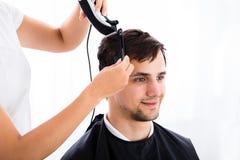 得到他的理发的人从美发师 免版税库存照片