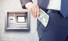 得到他的薪金的人从ATM机器 图库摄影
