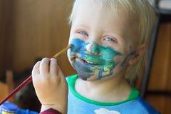 得到他的面孔的幼儿被绘 免版税库存图片