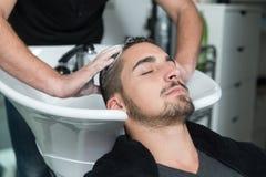 得到他的头发的男性客户画象洗 免版税库存照片
