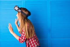 得到经验使用虚拟现实VR耳机玻璃姿势示意的手的愉快的妇女 免版税库存图片