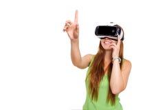 得到经验的愉快的微笑的年轻美丽的女孩画象使用虚拟现实VR耳机玻璃被隔绝 库存图片