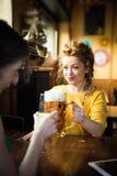 得到toghether饮用的啤酒和laughin的两个朋友,室内 免版税图库摄影