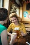 得到toghether饮用的啤酒和laughin的两个朋友,室内 免版税库存图片