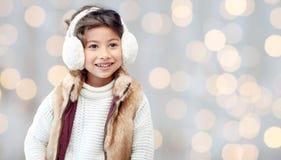 御寒耳罩的愉快的小女孩在假日点燃 免版税库存图片