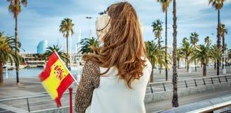 御寒耳罩的现代妇女在有西班牙旗子的巴塞罗那 免版税图库摄影