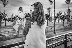 御寒耳罩的现代妇女在有西班牙旗子的巴塞罗那 库存图片