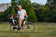 循环与父亲的自行车位子的逗人喜爱的女孩在城市 免版税库存照片