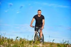 循环在一个绿色草甸的年轻人反对与云彩的蓝天 库存照片