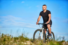 循环在一个绿色草甸的年轻人反对与云彩的蓝天 图库摄影