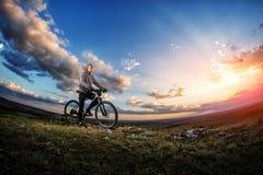 循环在一条农村路的年轻人通过草甸 免版税库存照片
