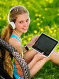 循环在个人计算机片剂的自行车女孩佩带的耳机手表 免版税库存图片
