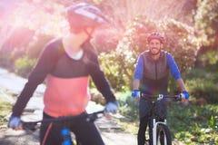 循环在乡下的骑自行车的人夫妇 库存照片
